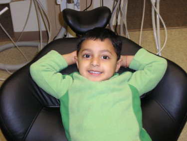 Image of smiling kid in dental office chair