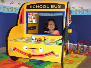 Image of a kid in a toy school bus at Fremont Dental Office